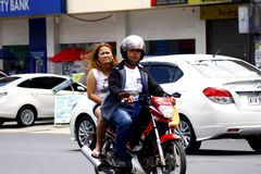 A man and a woman riding in tandem on a motorcycle in Antipolo City. Royalty Free Stock Photos