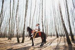 Man and a woman riding together brown horse Royalty Free Stock Photos