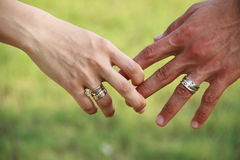 Man and Woman with Ring Couple Outdoors. Man and woman holding hands in outdoor natural setting with grass. Woman is wearing a diamond solitaire engagement ring Royalty Free Stock Photo