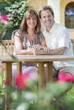 Man & Woman Romantic Couple In Garden. Attractive, romantic and happy middle aged men and women couple in their forties, sitting togther outside in a garden with Royalty Free Stock Photography