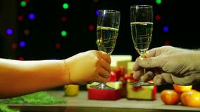 A man and woman romantically celebrate Christmas / New Year holding champagne glasses in their hands and hit them together stock video