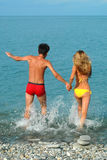 Man and woman run in the sea Royalty Free Stock Image
