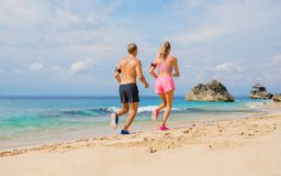 Man and woman run together on the beach Royalty Free Stock Photography