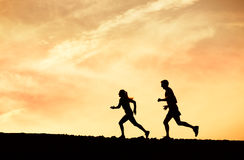 Man and woman runing together into sunset Stock Photos