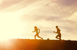 Man and woman runing together into sunset Royalty Free Stock Image