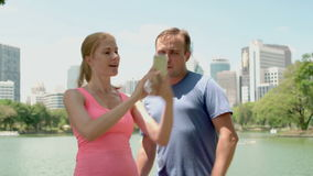 Man and woman runners jogging in park. Fit female male sport fitness running training. Making selfie. Handsome man and beautiful attractive woman runners jogging stock video