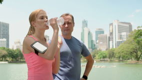 Man woman runners jogging in park. Fit female male sport fitness training. Drinking water from bottle. Handsome man and beautiful attractive woman runners stock footage