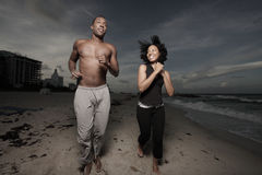Man and woman running on the beach Stock Image