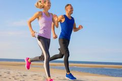 Man and woman running on beach royalty free stock photos
