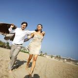 Man and woman running on beach Stock Photos