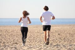 Man and woman running in the beach. Man and women running in the beach towards the sea Royalty Free Stock Photo
