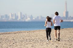 Man and woman running in the beach. Man and women running in the beach towards the sea with a city in background Royalty Free Stock Images