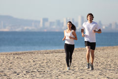 Man and woman running in the beach. Man and women running in the beach towards the sea with a city in background Royalty Free Stock Photos