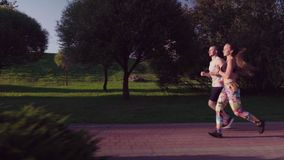 Man and woman running in city park. A man and a woman are running along the path in the city park stock video footage