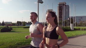 Man and woman running in city park stock video footage