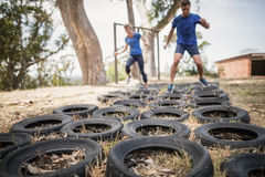 Man and woman running over the tyre during obstacle course. Man and women running over the tyre during obstacle course in boot camp royalty free stock photos