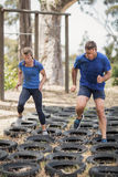 Man and woman running over the tyre during obstacle course. Man and women running over the tyre during obstacle course in boot camp royalty free stock image