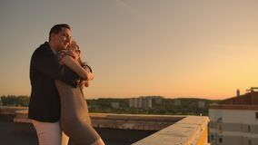 A man with a woman running on the roof holding hands. Slow motion lovers on the roof