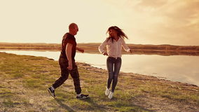 Man and woman running on sand stock footage
