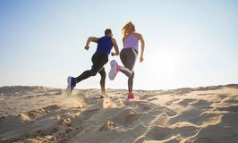 Man and woman running in sand stock photo
