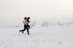 Man and woman running on the snow Stock Photography
