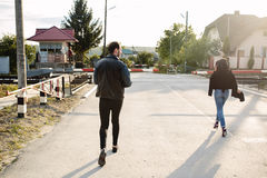 Man and woman running to the railroad crossing. Man and women running to the railway crossing in the street Stock Image
