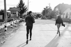 Man and woman running to the railroad crossing. Man and women running to the railway crossing in the street Stock Images