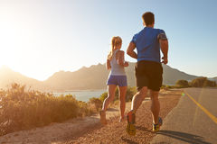 Man and woman running together on an empty road Stock Photo