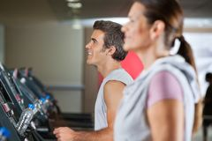 Man And Woman Running On Treadmill Royalty Free Stock Photos