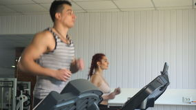 Man and woman running on treadmill stock video footage