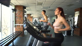 Man and woman running on treadmill. Sportsman man and woman running on treadmill in the gym stock video