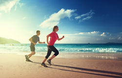 Man and woman running on tropical beach Royalty Free Stock Image
