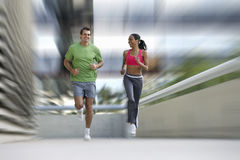 Man and woman running on urban sidewalk Stock Photo