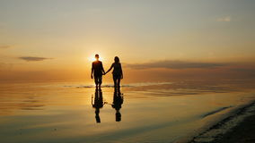 Man and woman running through the water to the camera. Fly spray at sunset stock video footage