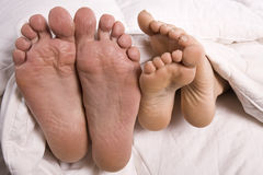Man and woman's feet in bed Stock Images