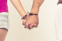 Man and woman's hands handcuffed together. Concept of love relationship romance sex crime punishment prison isolated on white Stock Photography