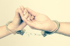 Man and woman's hands handcuffed together. Holding hands concept of love relationship romance sex crime punishment prison isolated on white Stock Image