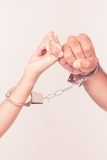Man and woman's hands handcuffed together. Holding pinky fingers together concept of love relationship romance sex crime punishment prison isolated on white Royalty Free Stock Photo