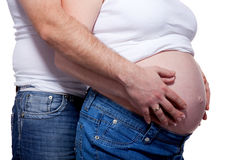 Man and woman's hands over pregnant belly Royalty Free Stock Images