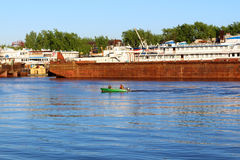 Man and woman sail on motorboat near old rusty ship Stock Photo