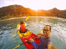Man and woman sailing sea kayak over clear water of island stock images