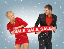 Man and woman with sale sign Stock Photos