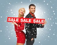 Man and woman with sale sign Royalty Free Stock Photos