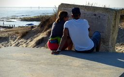 A man and a woman sat, seen from behind of forehead to a stone with some text and after all the sea. Andalusia. Spain. A man and a woman sat, seen from behind of royalty free stock photos