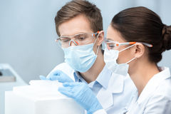 Man and woman scientists in protective glasses and masks making experiment Royalty Free Stock Photos