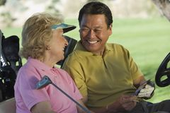 Man And Woman With Scorecard. Happy men and women with scorecard sitting in golf cart Stock Images