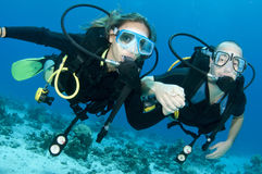 Man and woman scuba dive togeather. Romantic couple scuba dive together in the ocean on a coral reef Stock Photos