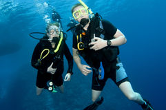 Man and woman scuba dive togeather. Romantic couple scuba dive together in the ocean on a coral reef stock image