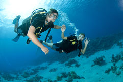 Man and woman scuba dive togeather. Romantic couple scuba dive together in the ocean on a coral reef stock photo