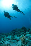 Man and woman scuba dive togeather. Romantic couple scuba dive together in the ocean on a coral reef stock photography